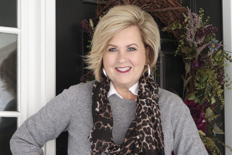 Fashion Blogger 50 Is Not Old is mixing a classic cashmere gray sweater and a trendy leopard scarf