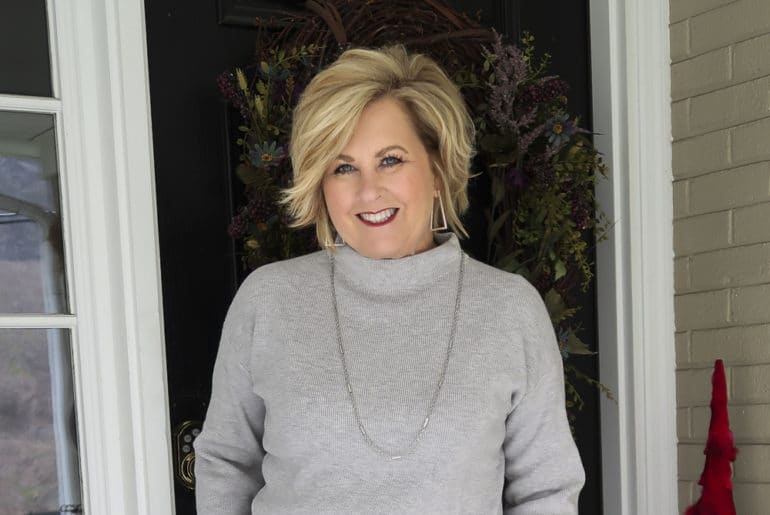 Fashion Blogger 50 Is Not Old wearing a gray side-tie sweater