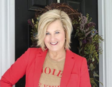 Fashion Blogger 50 Is Not Old wearing a red blazer and a tan sweater