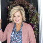 Fashion Blogger 50 Is Not Old is wearing a blue floral blouse and a chunky knit cardigan