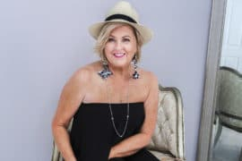 Fashion Blogger 50 Is Not Old is wearing a black jumpsuit with statement earrings, and a fedora
