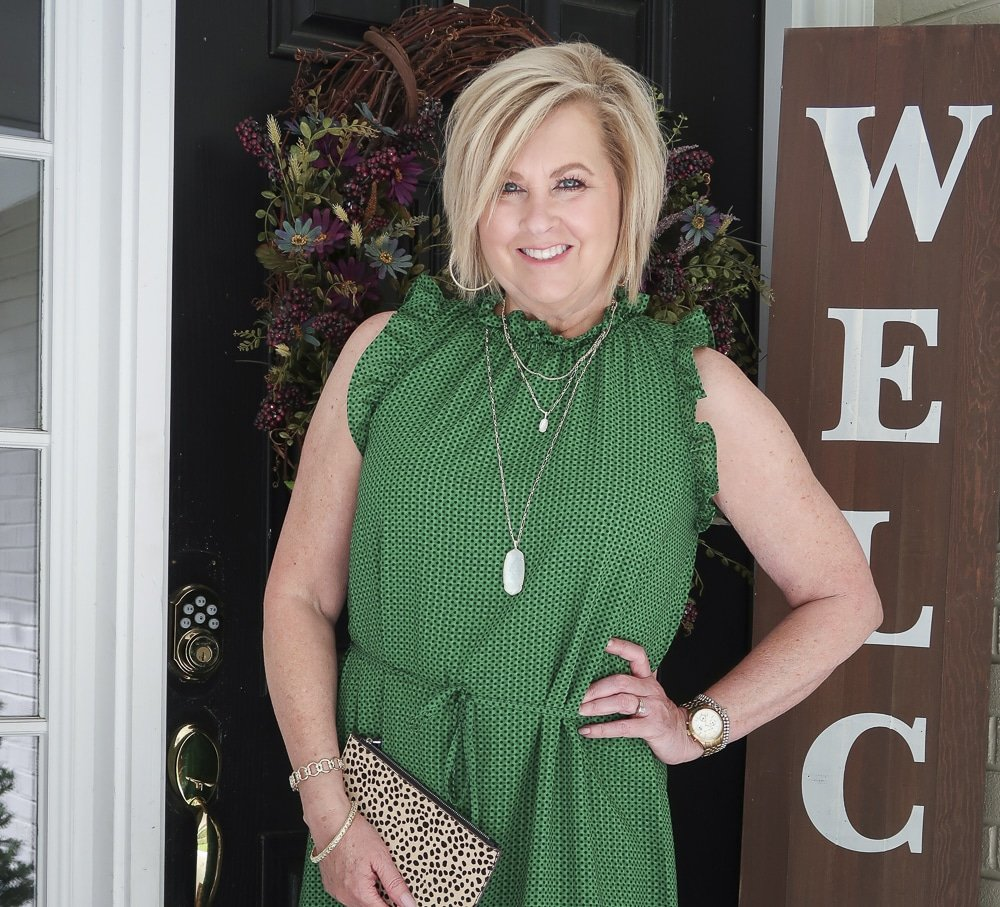 Fashion Blogger 50 Is Not Old is wearing a green polka dotted dress that has a high neck and ruffles