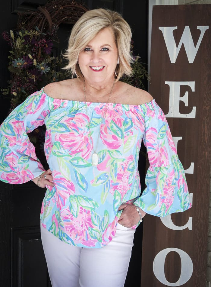 Fashion Blogger 50 Is Not Old wearing a colorful off the shoulder top from Lilly Pulitzer