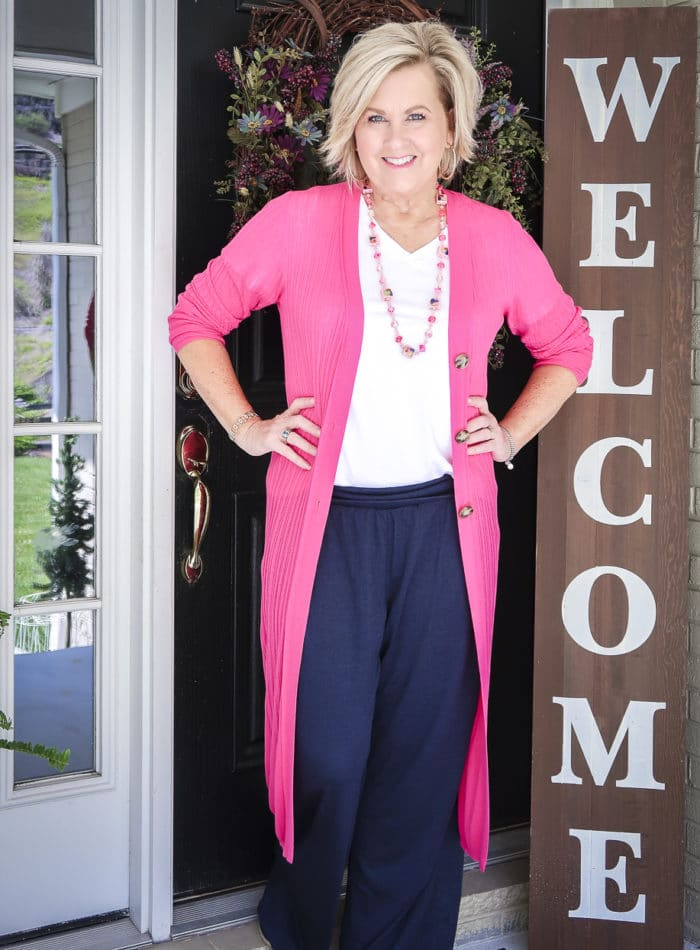 Fashion Blogger 50 Is Not Old wearing a hot pink duster cardigan with a white t-shirt, and navy lounge pants