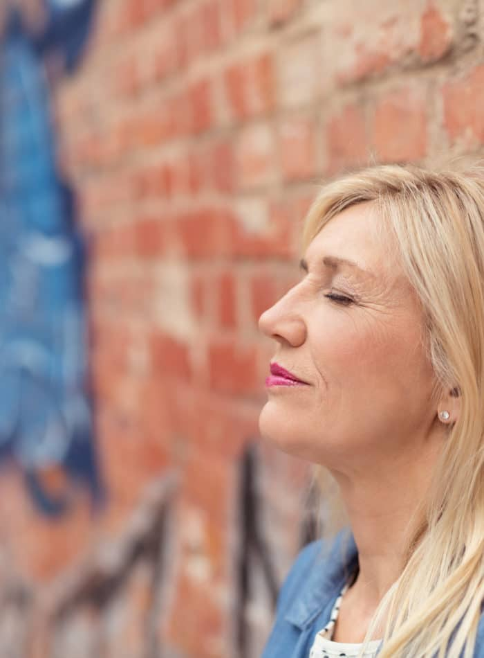 Woman relaxing against a brick wall dreaming