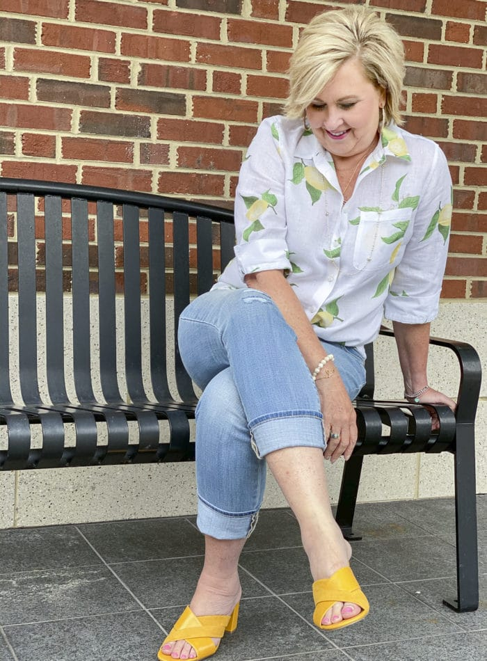 Fashion Blogger 50 Is Not Old is wearing a white button down shirt with yellow lemons, a pair of distressed girlfriend jeans, and yellow block heel sandals