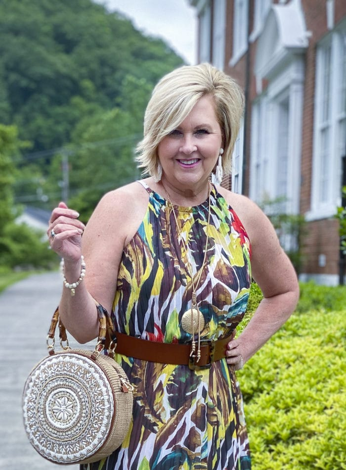 Fashion Blogger 50 Is Not Old is wearing a beautiful tropical dress from Chico's with a circle handbag