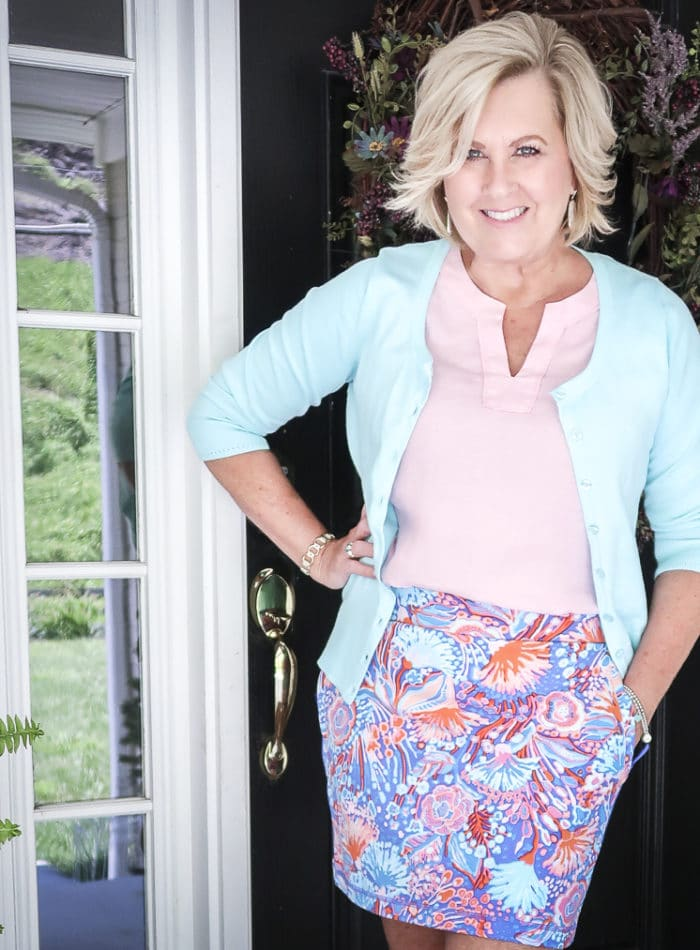Fashion Blogger 50 Is Not Old is wearing a pale linen v neck top, an aqua colored cardigan, and a colorful skort from Talbots