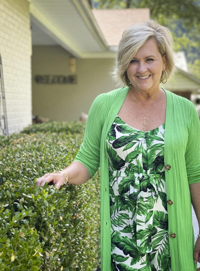 Fashion Blogger 50 Is Not Old is wearing a tropical banana leaf print jumpsuit with a long bright green cardigan