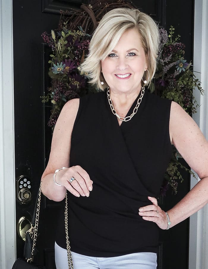 Fashion Blogger 50 Is Not old is wearing a black faux wrap top