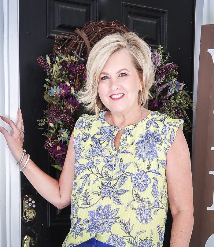 Fashion Blogger 50 Is Not Old wearing a yellow top with a blue floral design