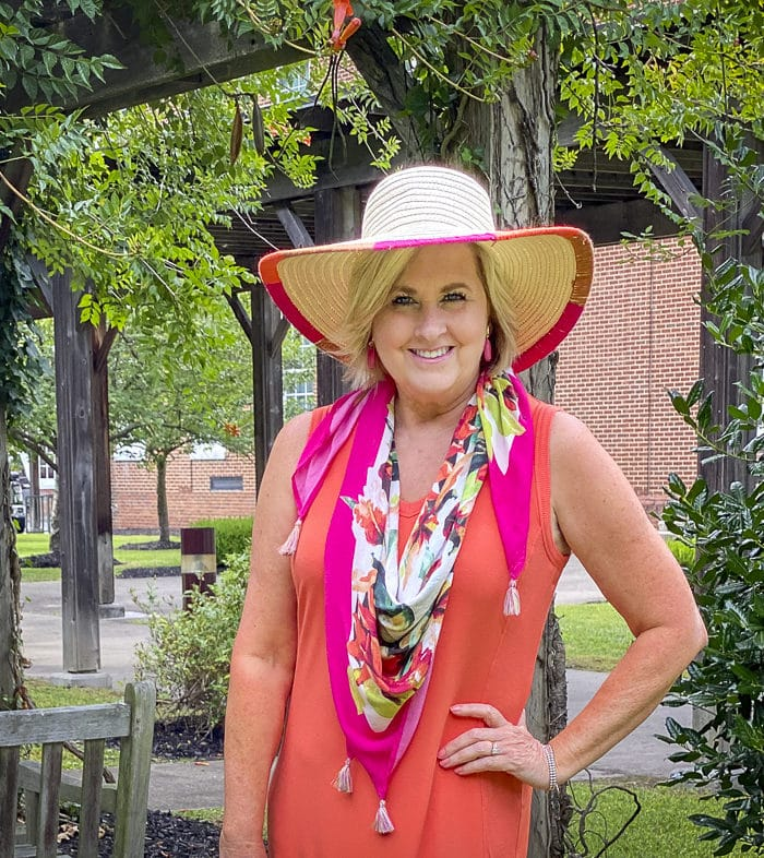 Fashion Blogger 50 Is Not Old is wearing an orange midi dress with a tropical print scarf in pink, a yarn trimmed straw hat
