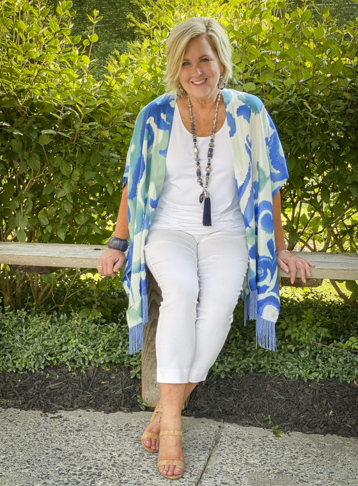 Fashion Blogger 50 Is Not Old is sitting on a bench wearing a white tank top, white textured crop pants, and a colorful silk ruana from Chicos with a long navy necklace and bamboo heels