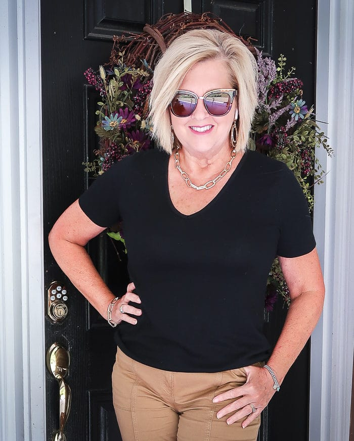 Fashion Blogger 50 Is Not Old is wearing a black v-neck t-shirt and gold link statement jewelry from Kendra Scott