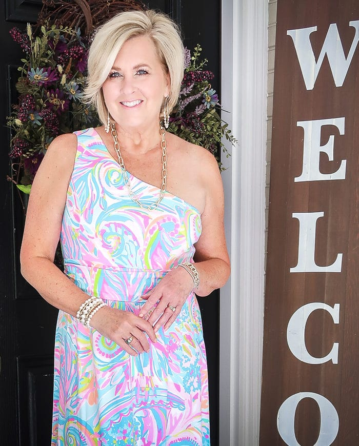 Fashion Blogger 50 Is Not Old is styling a one shoulder Lilly Pulitzer maxi dress with jewelry from Kendra Scott