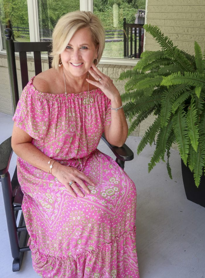 Fashion Blogger 50 Is Not Old is sitting in a rocking chair and wearing an off the shoulder pink dress with delicate gold jewelry and gold wedge espadrilles