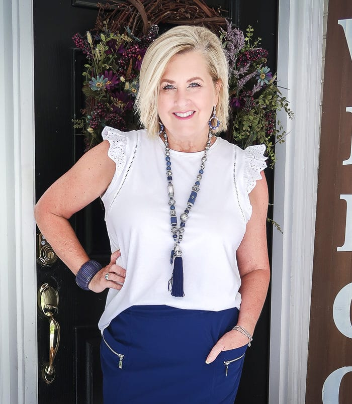 Fashion Blogger 50 Is Not Old is wearing an eyelet flutter sleeve top with a navy skort with zippers