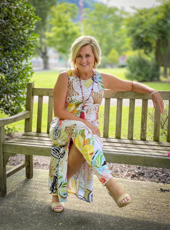 Fashion Blogger 50 Is Not Old is sitting on a bench wearing a tropical print sleeveless dress with colorful accessories and white espadrilles