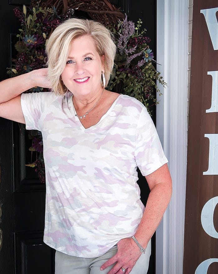 Fashion Blogger 50 Is Not Old is leaning against a door while wearing a mute camo top is purple and green