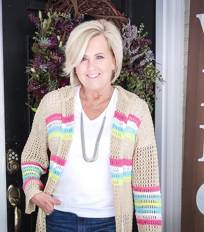 Fashion Blogger 50 Is Not Old is wearing a white v neck t-shirt, distressed jean shorts, and a open knit long cardigan