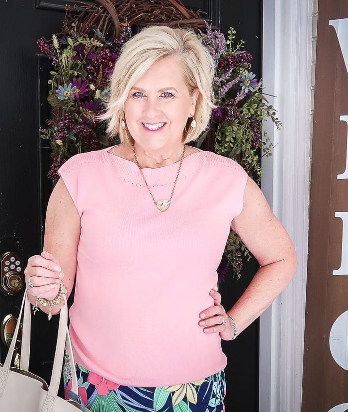 Fashion Blogger 50 Is Not Old is wearing a cap sleeve pink sweater