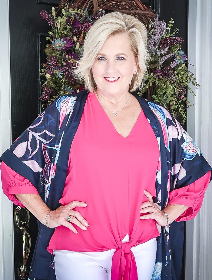 Fashion Blogger 50 Is Not Old is bright and colorful in a tie-front pink blouse, and a floral navy ruana