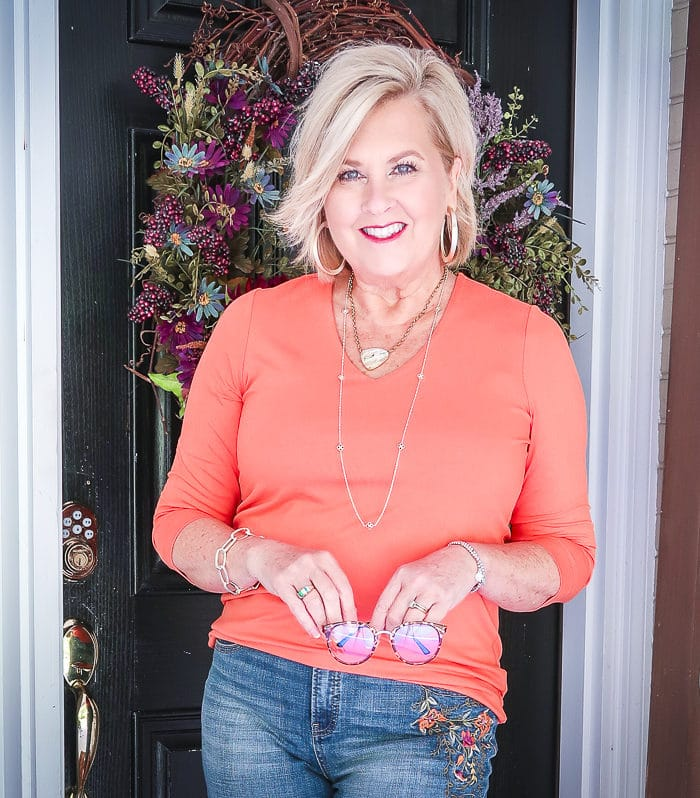 Fashion Blogger 50 Is Not Old is wearing a rust orange v-neck top from Chicos