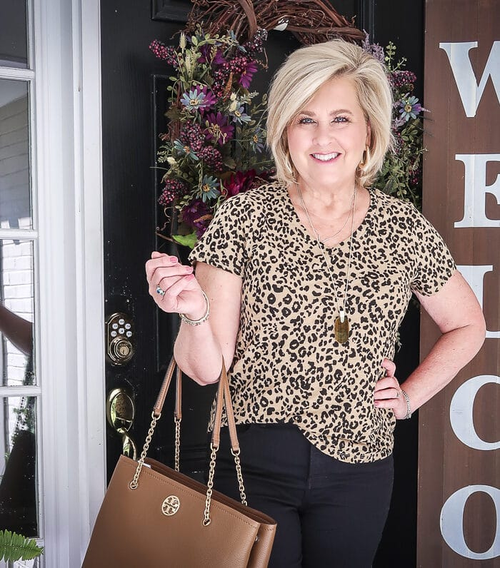 Fashion Blogger 50 Is Not Old is wearing a v-neck leopard tee, black girlfriend jeans, and carrying a brown Tory Burch tote