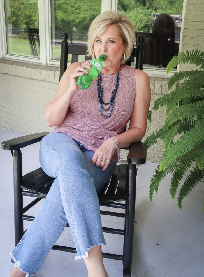 Fashion Blogger 50 Is Not Old is drinking her Sprite and is ready for celebrating Labor Day in her red white and blue top twist top, distressed jeans, and Sperry sneakers