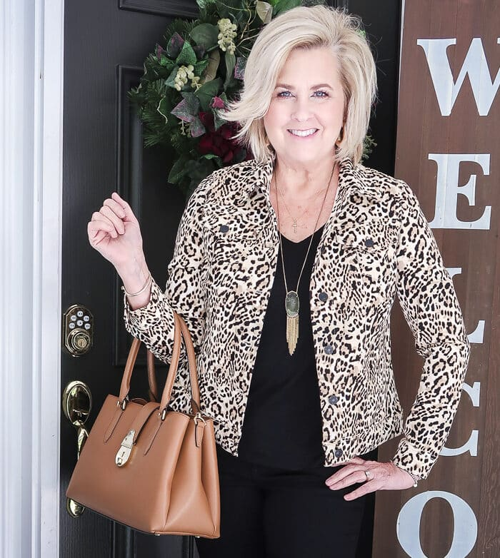 Fashion Blogger 50 Is Not Old is looking sharp in this cheetah print denim jacket and a black tee and carrying a caramel handbag