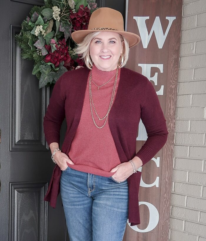 Fashion Blogger 50 Is Not Old is wearing a brown Fedora with a maroon cardigan, a rose colored sweater and blue jeans
