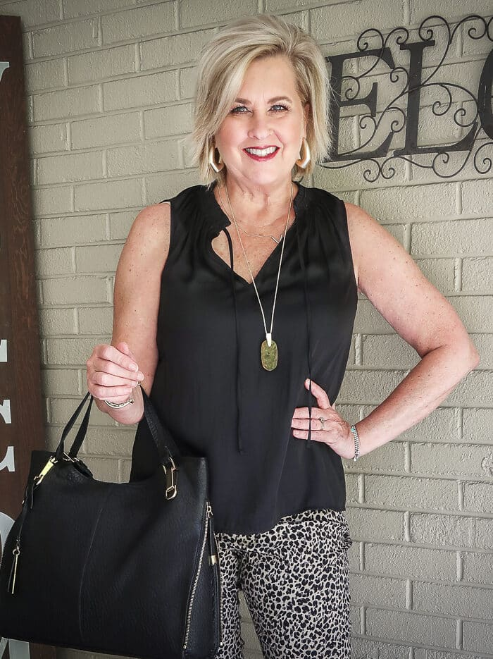 Fashion Blogger 50 Is Not Old is wearing a black smocked tank top, a pair of animal print pants, and a black lambskin tote