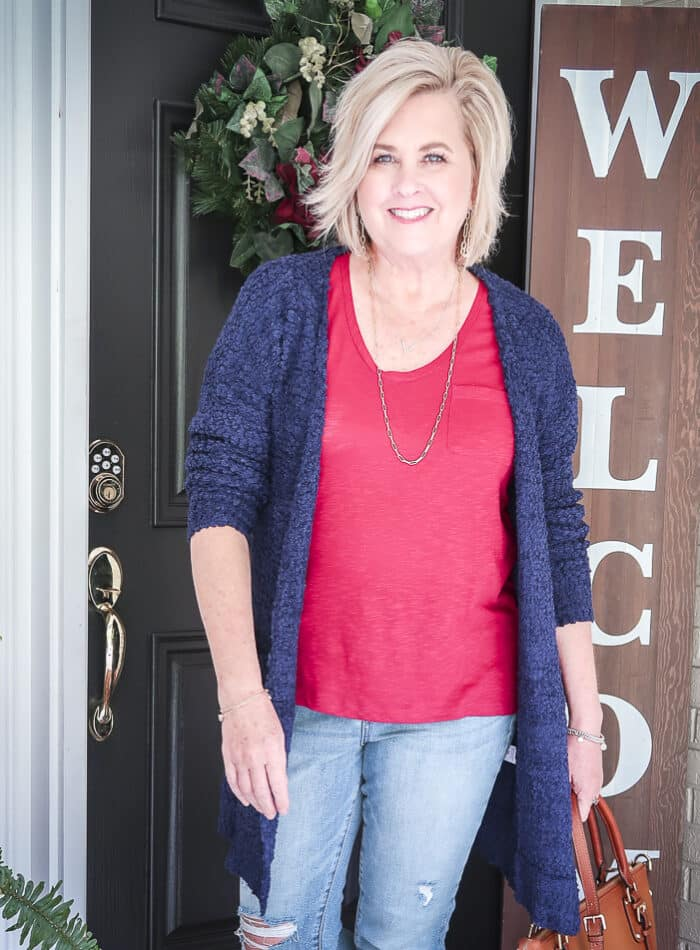 Fashion Blogger 50 Is Not Old is weekend ready in her burgundy t-shirt, distressed jeans, and a chunky knit cardigan