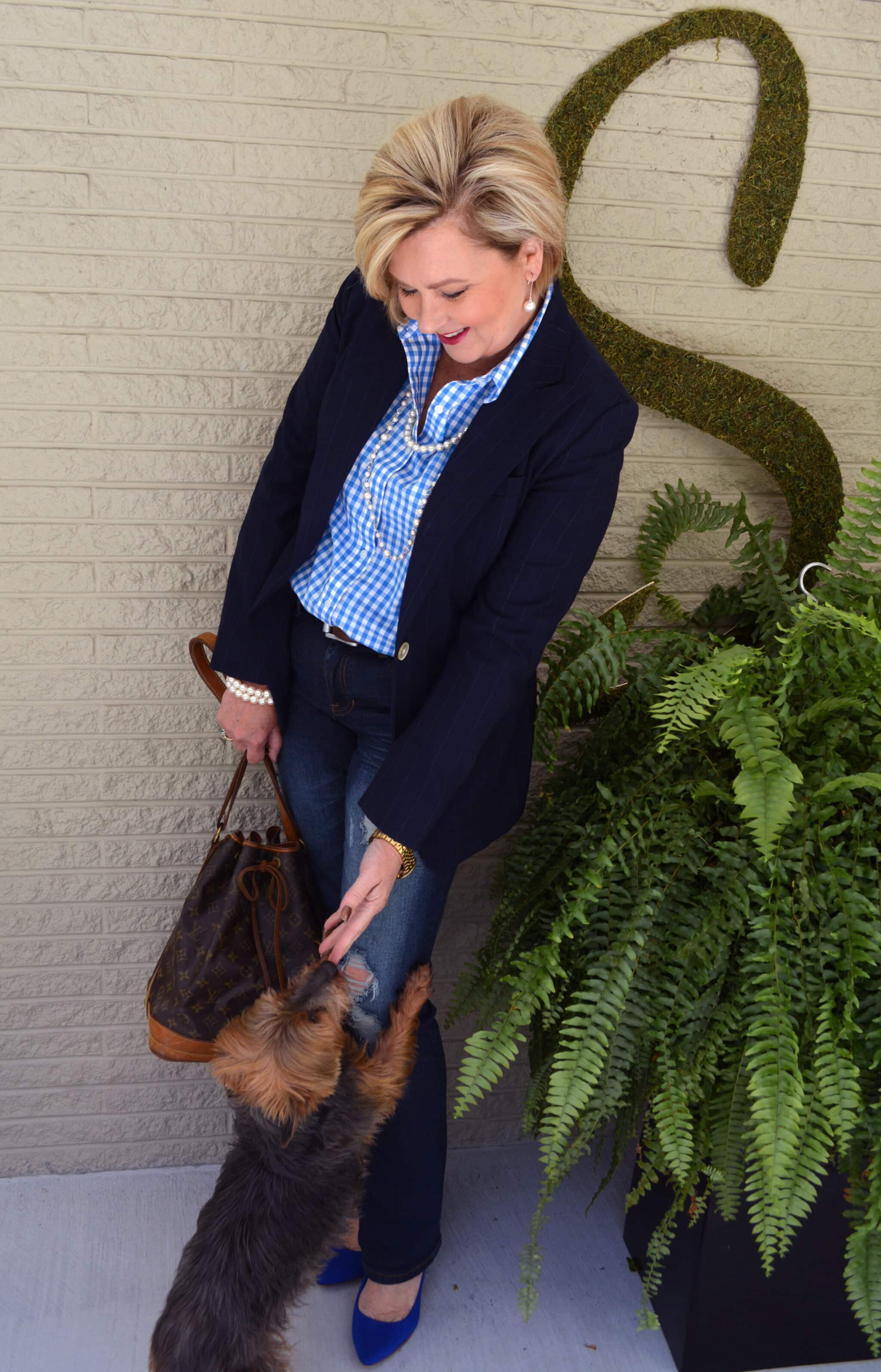 Over 40 Fashion Blogger, Tania Stephens, in a gingham shirt and navy blazer with a Yorkie dog