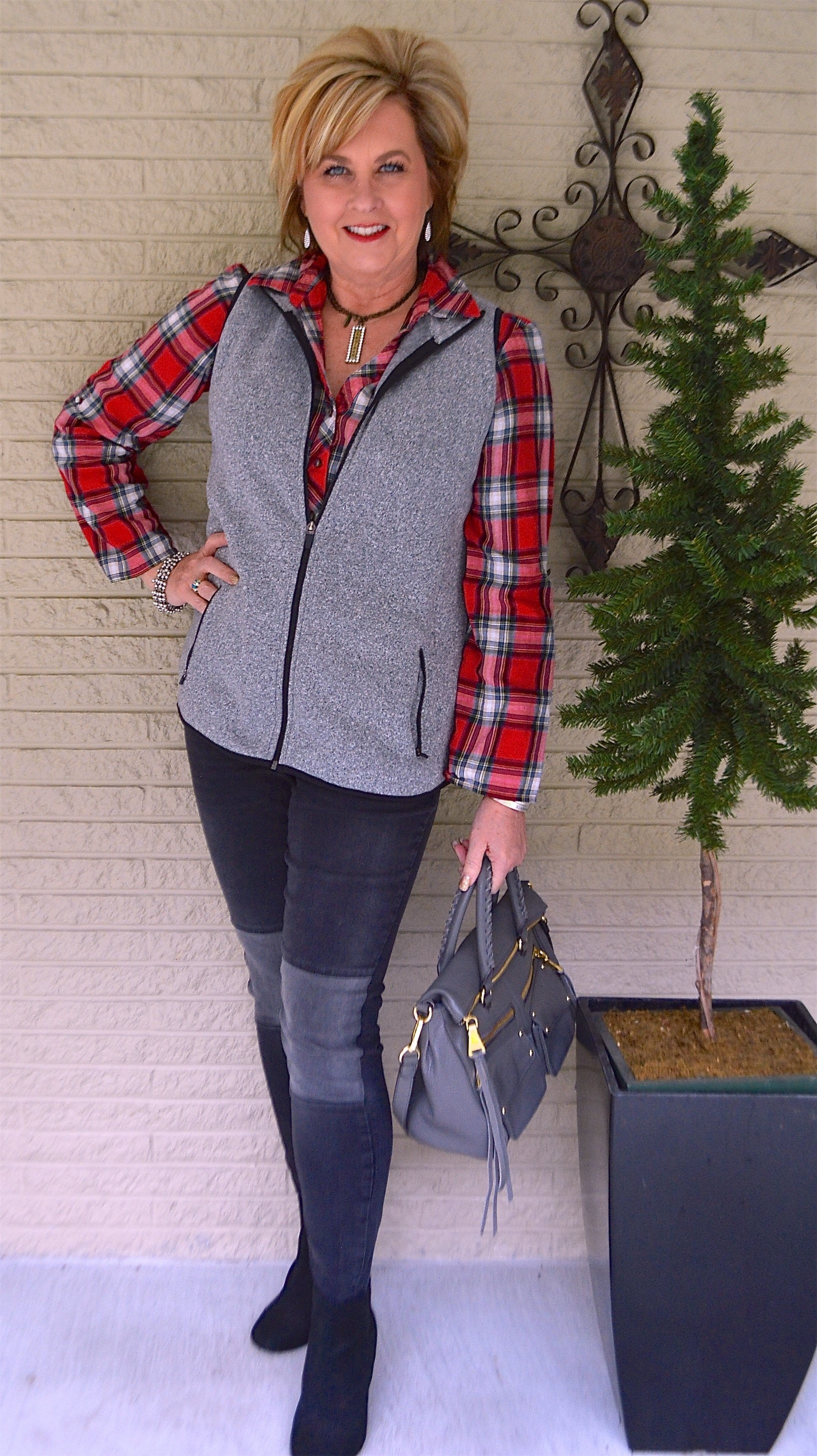 Fashion Blogger 50 Is Not Old in a red plaid shirt, a gray vest, and black jeans
