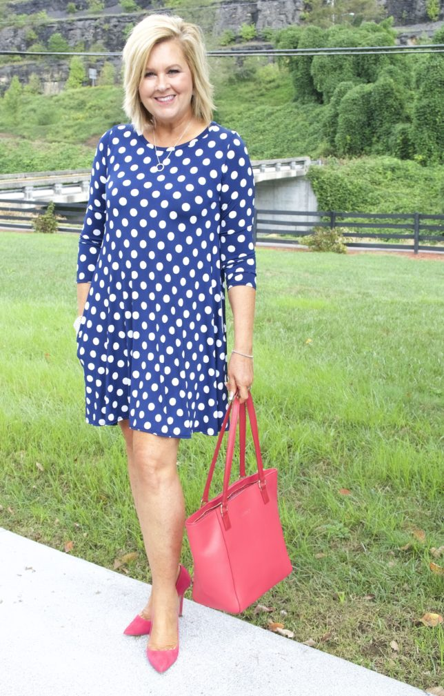 Fashion Blogger 50 Is Not Old is wearing a blue and white polka dot dress with a pink Vera Bradley tote