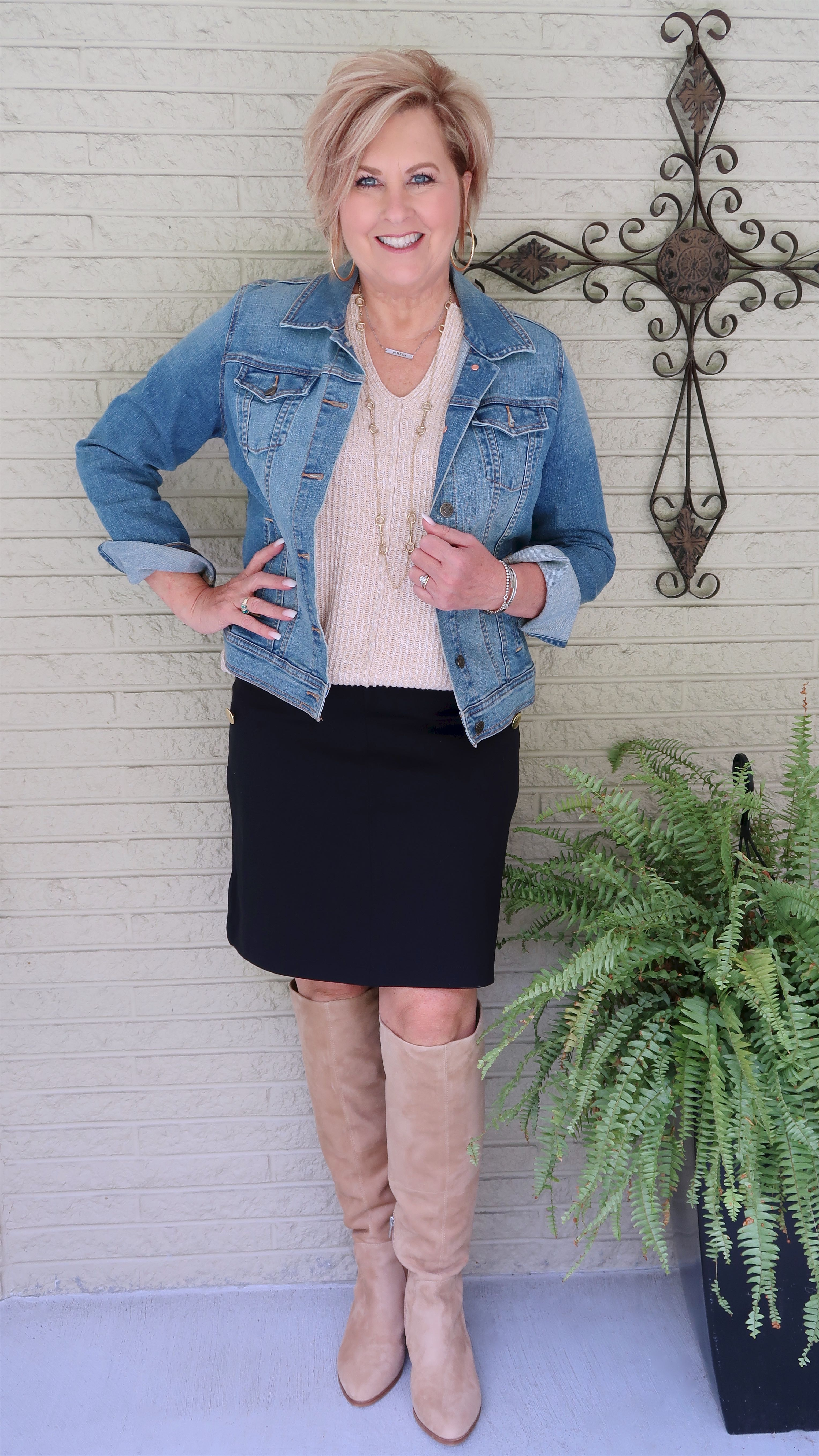 Fashion Blogger 50 Is Not Old in a denim Jacket, a navy skirt, and knee boots