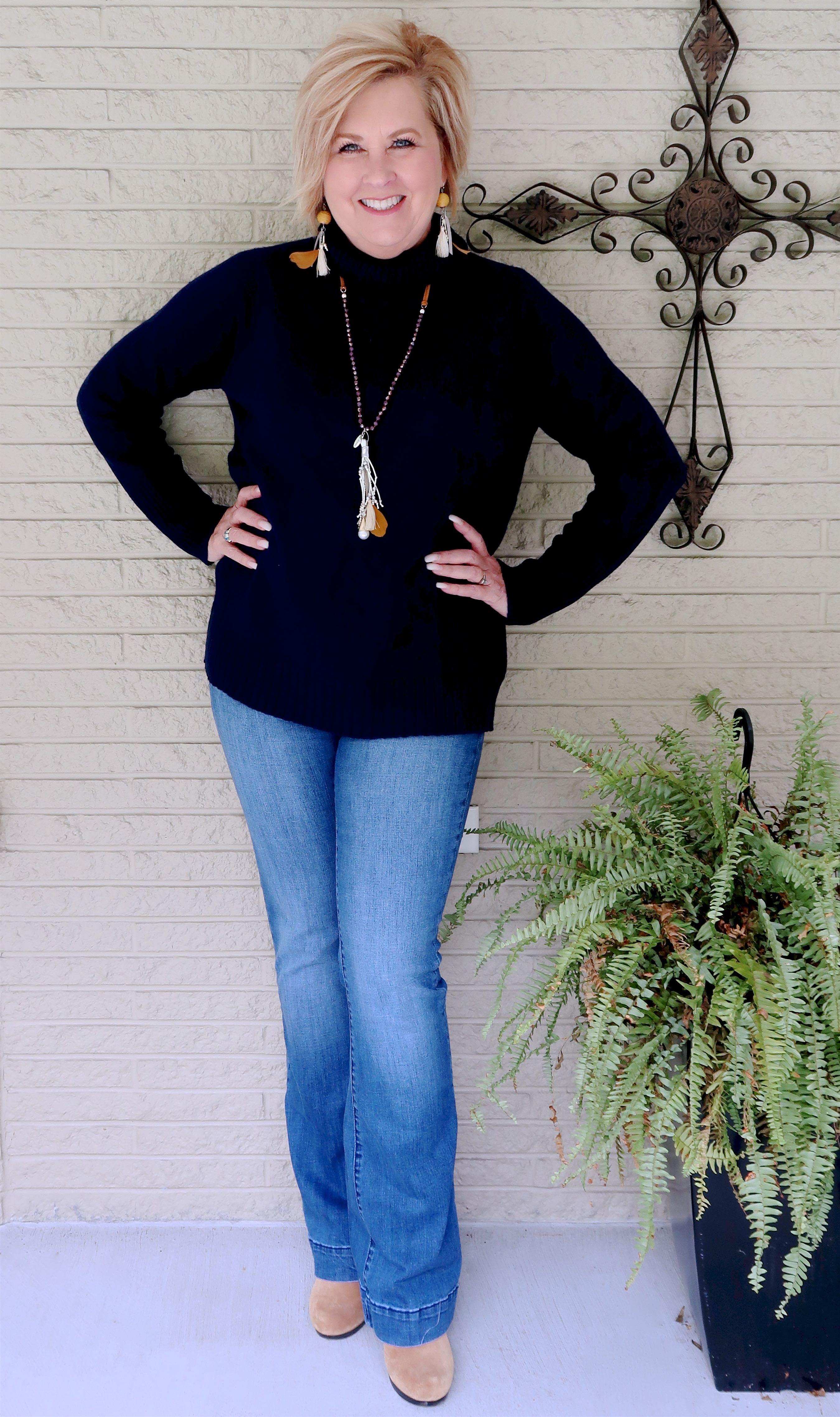 Fashion Blogger 50 Is Not Old in a navy turtleneck sweater, flare jeans, and boots