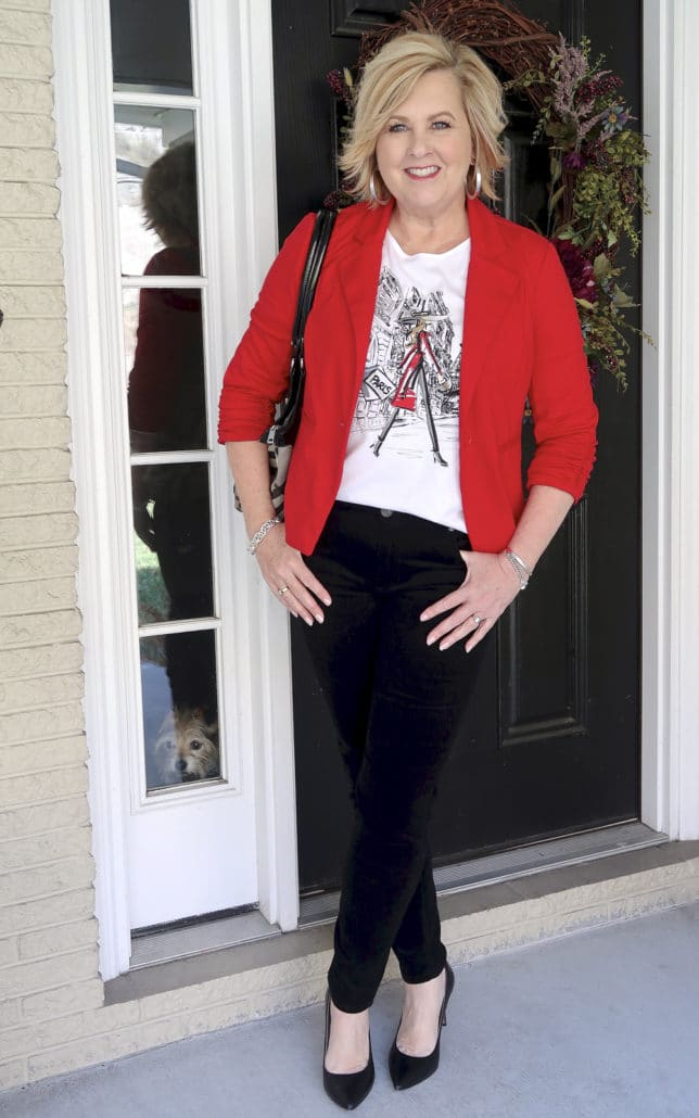 Fashion Blogger 50 Is Not Old looks stylish in a graphic tee and black velvet pants