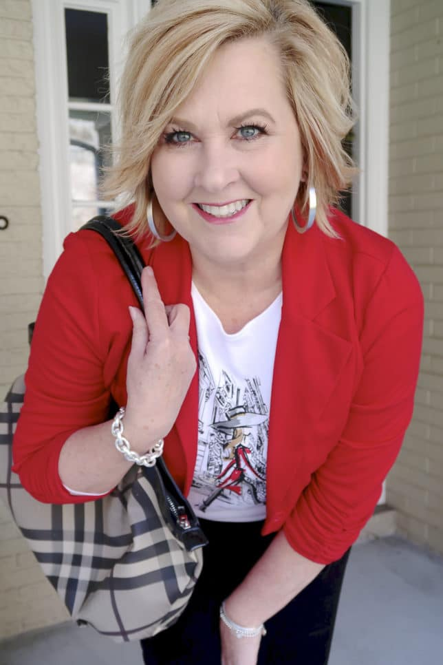 Fashion Blogger 50 Is Not Old looks stylish in a graphic tee with a red jacket