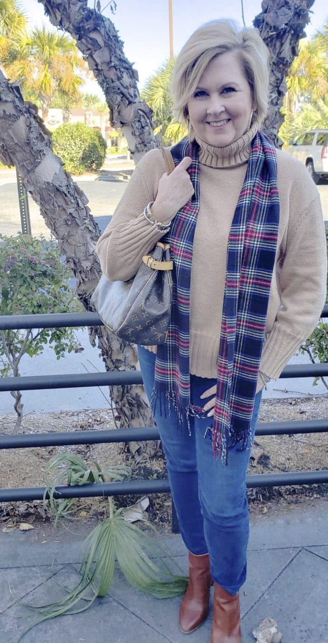 A beige turtleneck with a plaid scarf