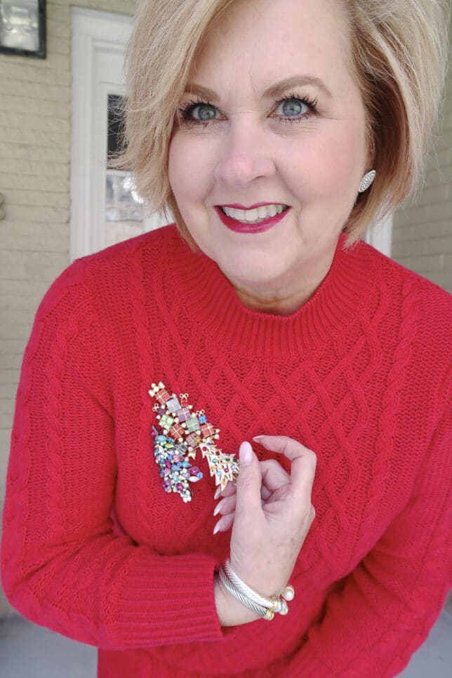 Fashion Blogger 50 is not old wearing a red sweater dress showing vintage Christmas tree pins