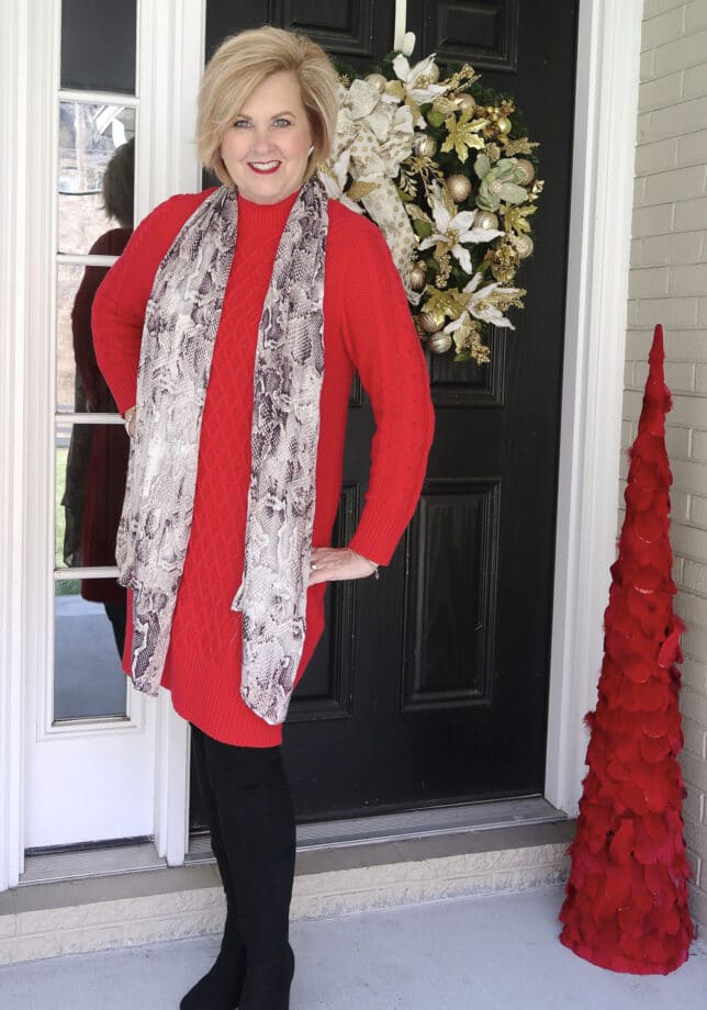 Fashion Blogger 50 is not old wearing a red sweater dress in front of a black door