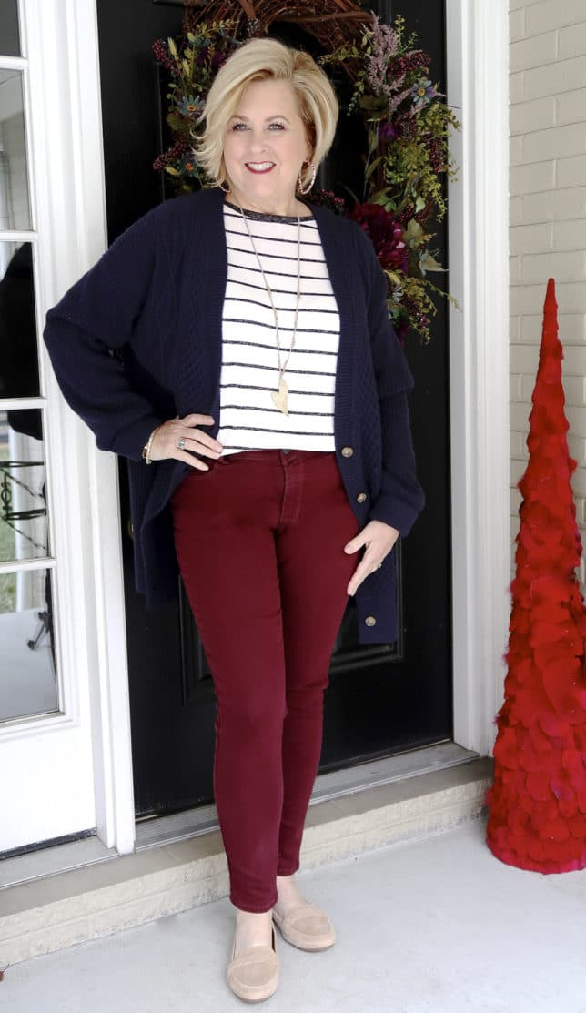 The unique details of the navy cardigan looks great with the burgundy jeans worn by 50 Is Not Old