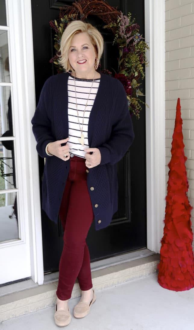 The unique details of the navy cable knit cardigan and the beige suede loafers look great with the burgundy jeans worn by 50 Is Not Old