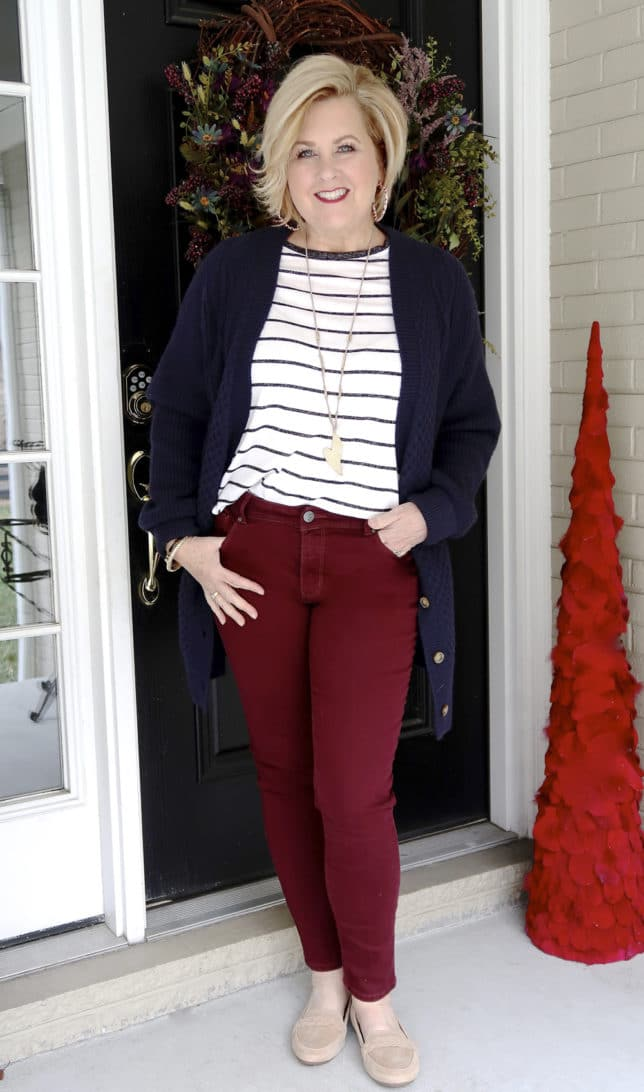 Fashion Blogger 50 Is Not Old wearing a stripe sweater with a navy cardigan and burgundy jeans