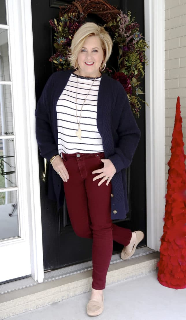 The unique details of the navy cable knit cardigan, the striped top, and the suede loafers look great with the burgundy jeans worn by 50 Is Not Old