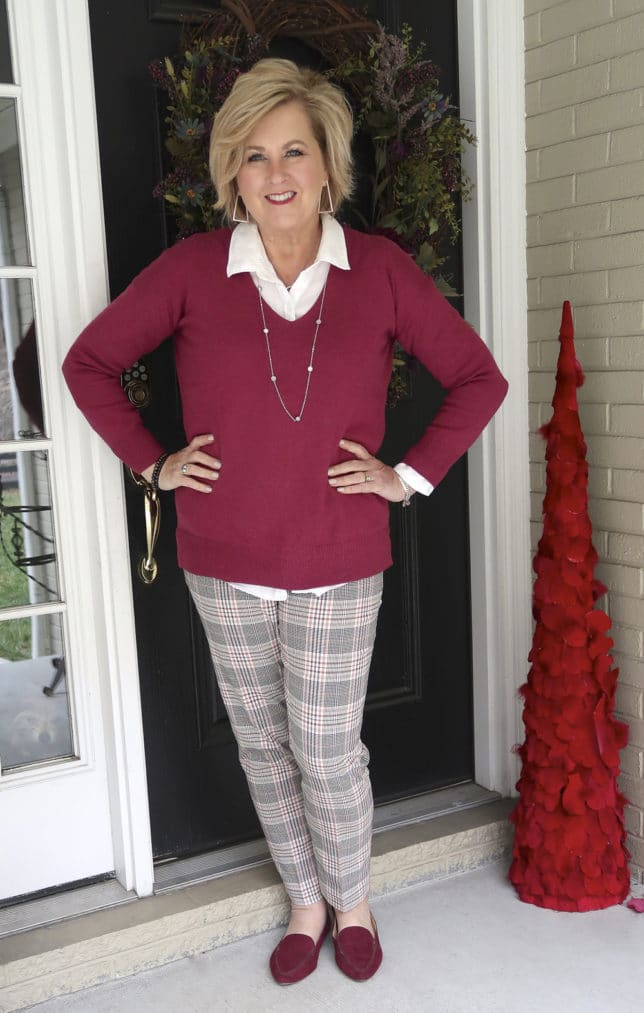 Fashion Blogger 50 Is Not Old is wearing a v neck sweater in a solid color, plaid pants, and loafers
