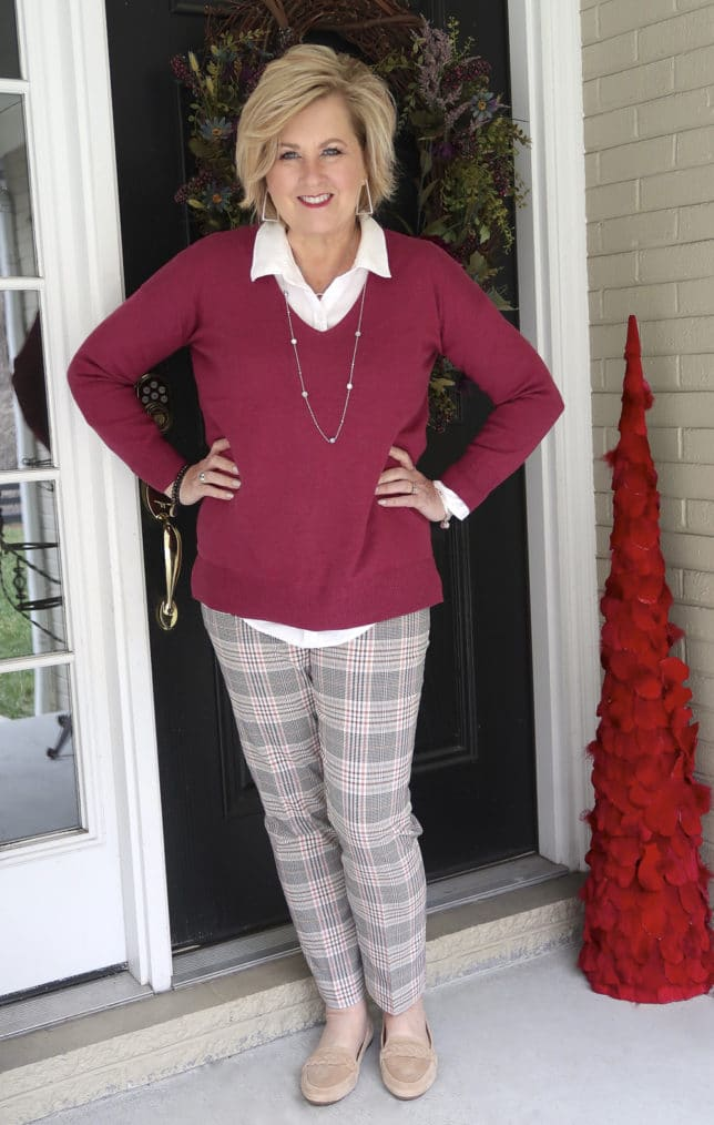 Fashion Blogger 50 Is Not Old is wearing a magenta v neck sweater in a solid color, plaid pants, and neutral loafers by Born