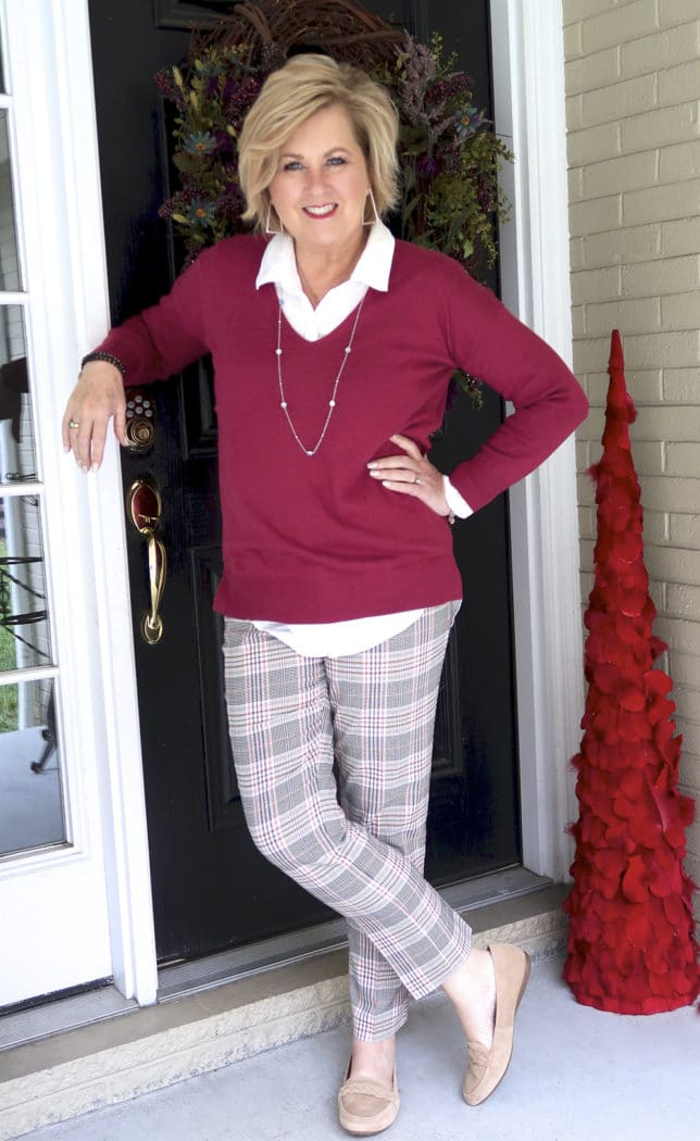 Fashion Blogger 50 Is Not Old is wearing a v neck sweater in a solid color and plaid pants